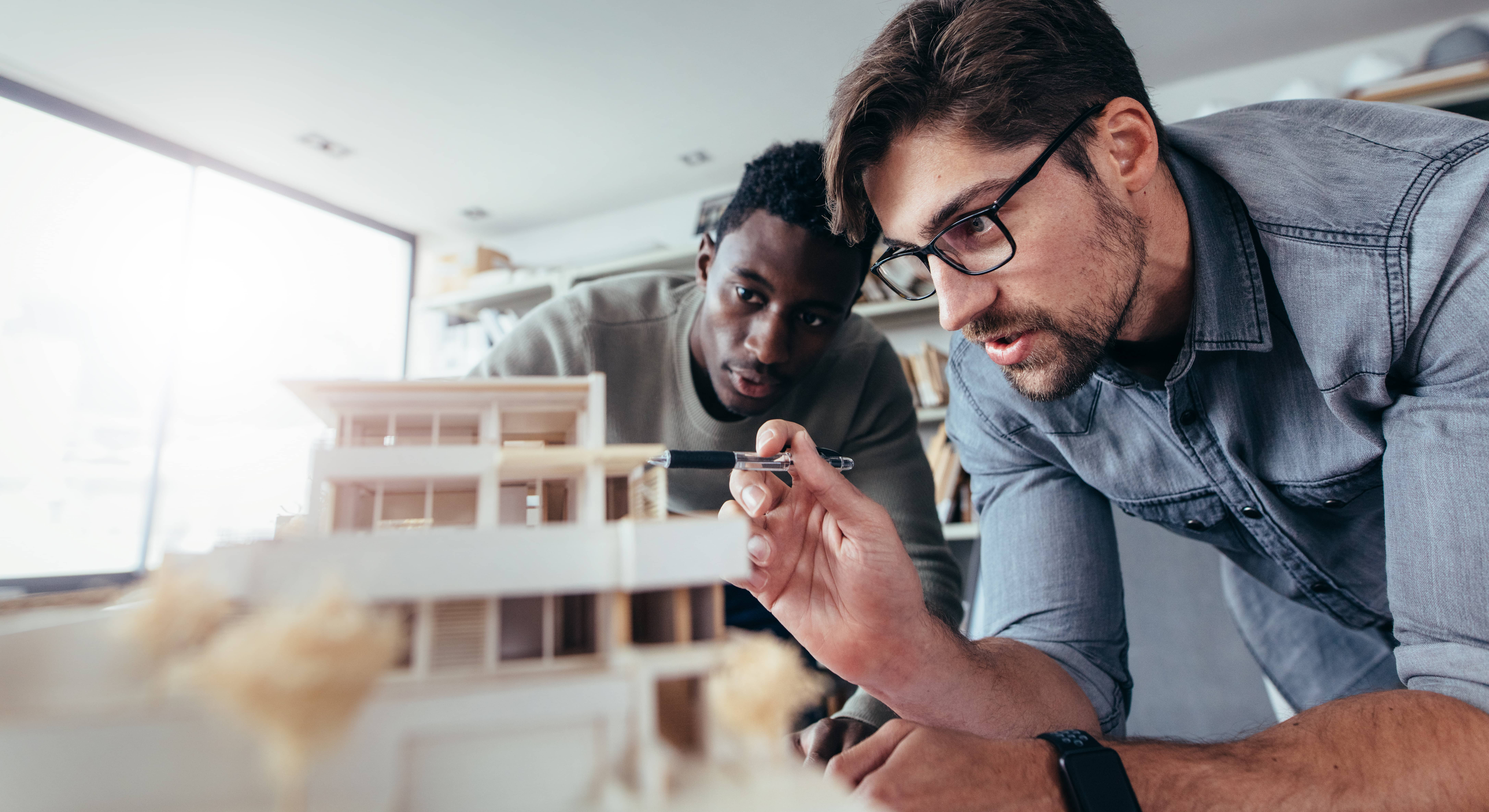 Two architects working on a model