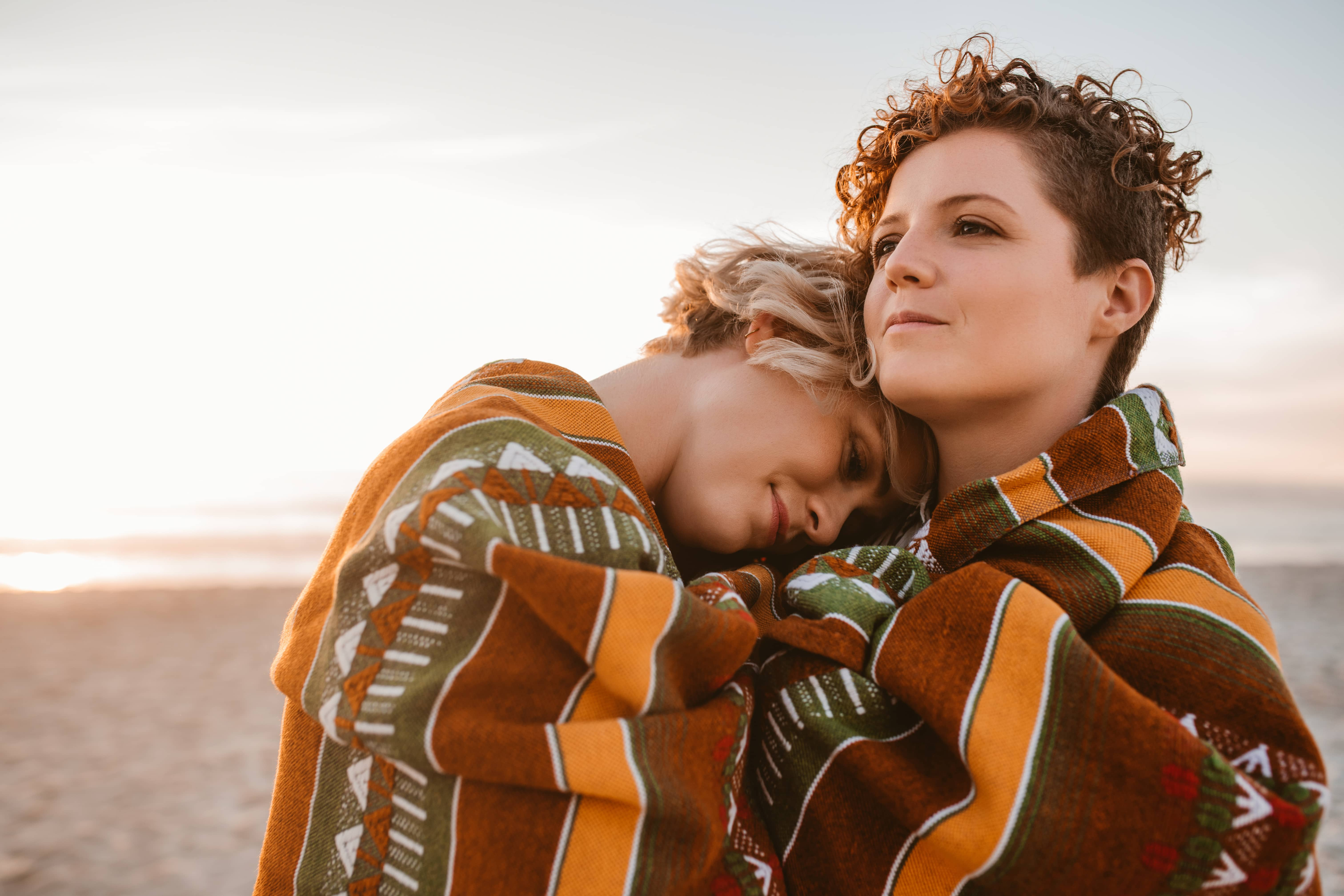 Two women wrapped in colorful wool blanket