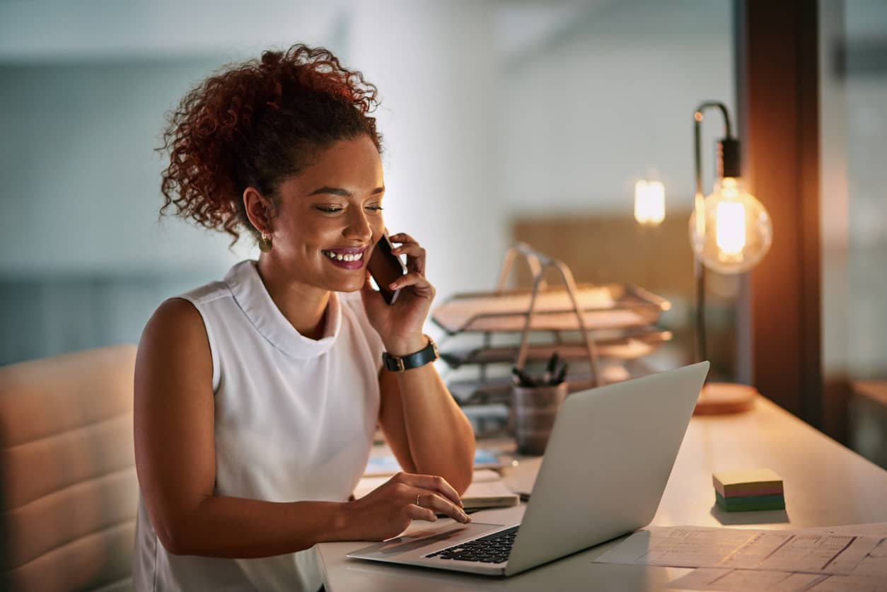 Entrepreneur working on her computer while on phone