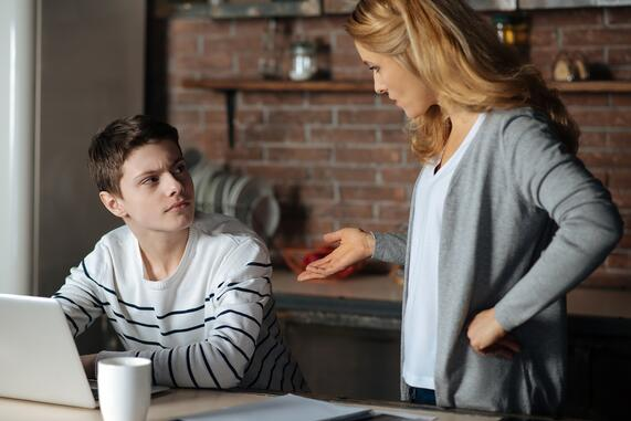 Teenager at a computer while engaging his mother