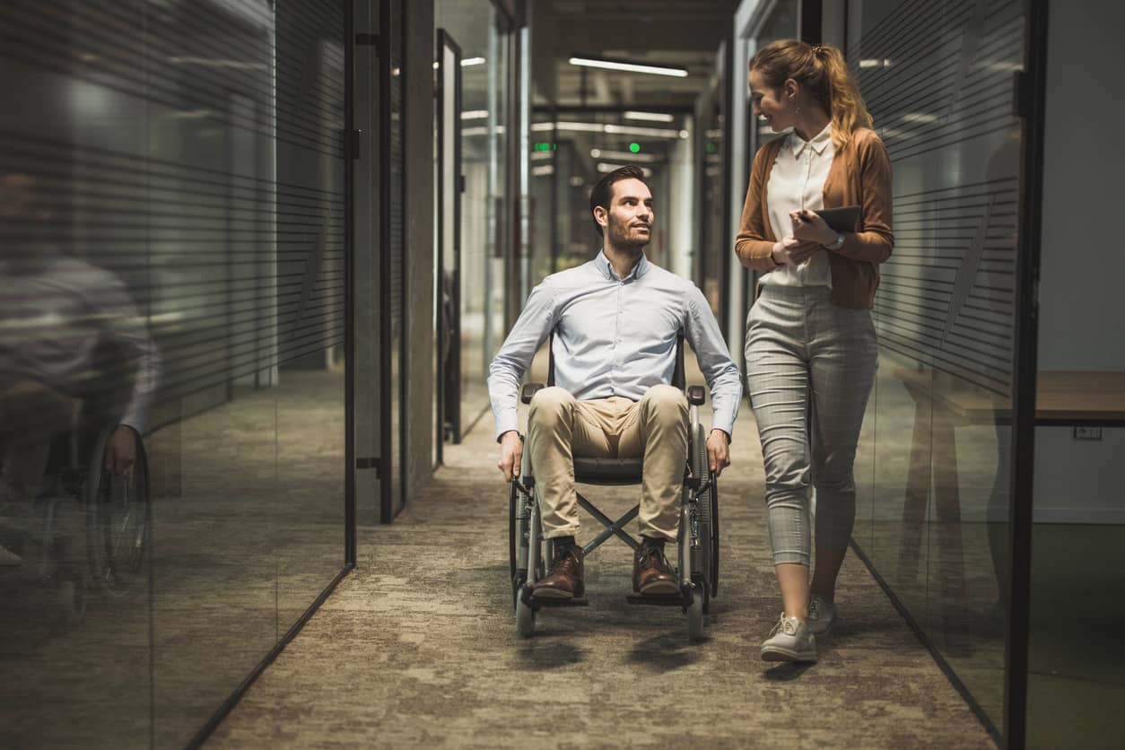 A businessman in a wheelchair talking a colleague at an inclusive workplace