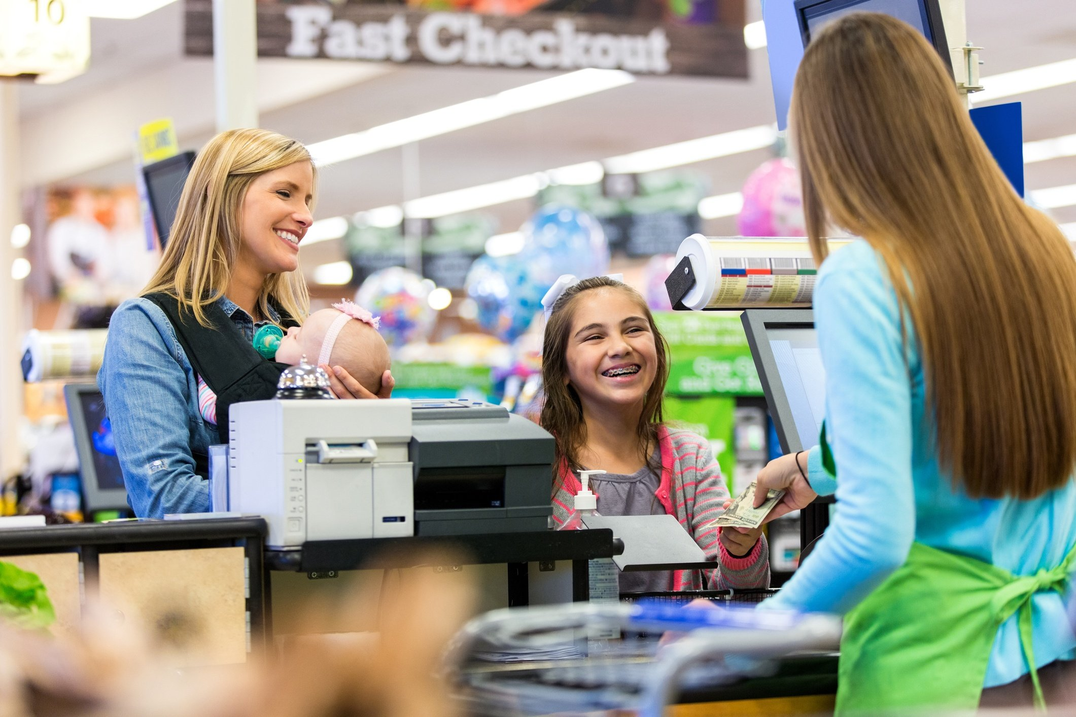 Cashier-giving-change-to-young-customer-in-grocery-store-501746150_2125x1416.jpeg