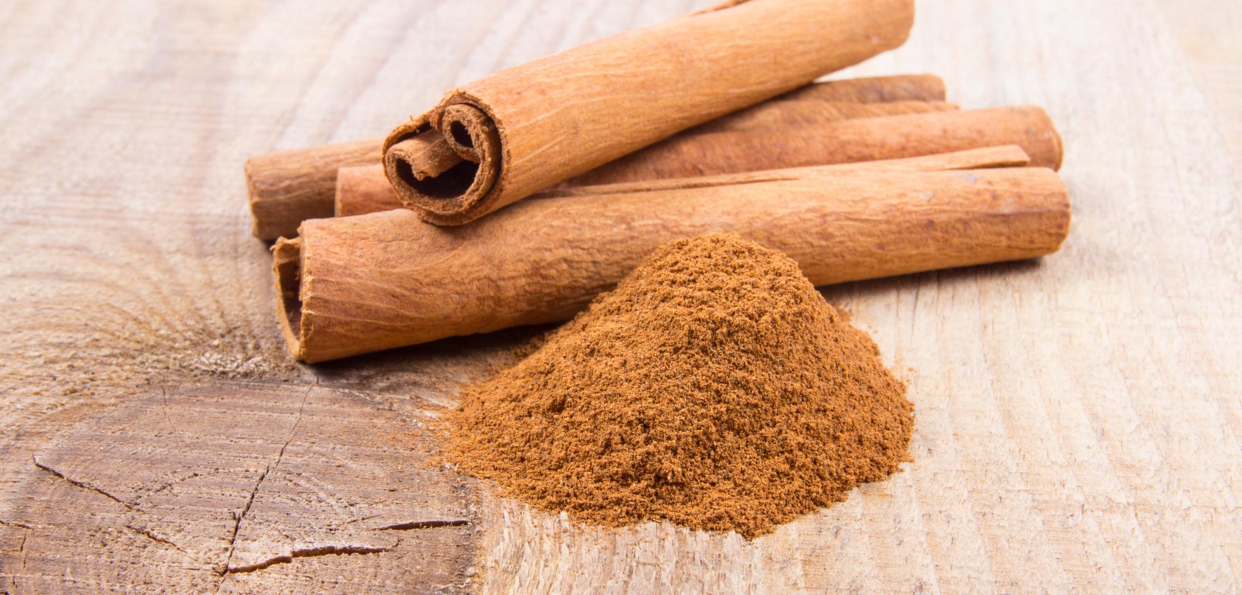 Cinnamon sticks laying on wooden block