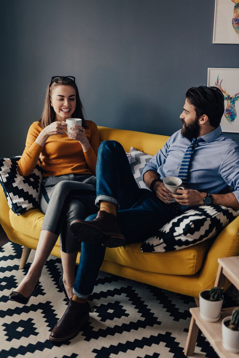 Couple sitting on a loveseat drinking tea and conversing