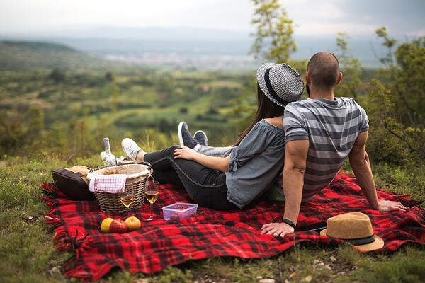A married couple enjoying a picnic overlooking a vista