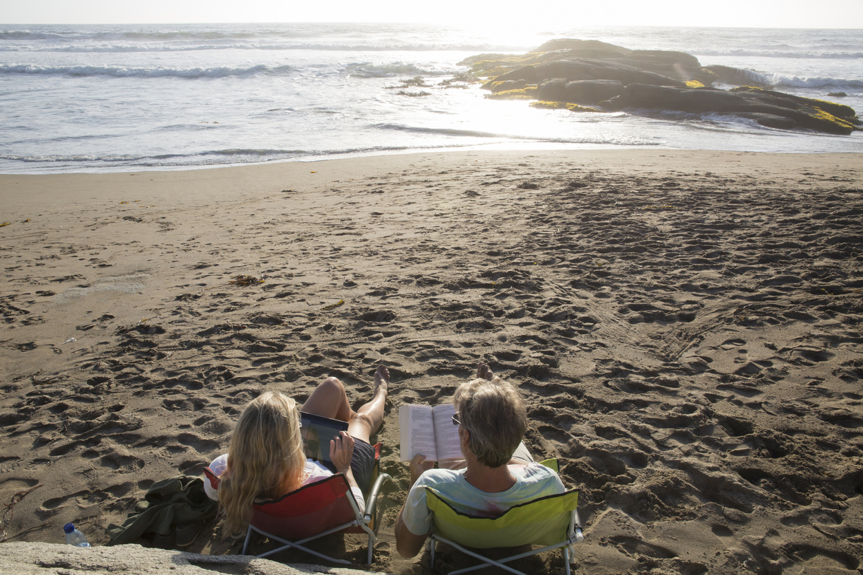 A couple reading on the beach at sunset