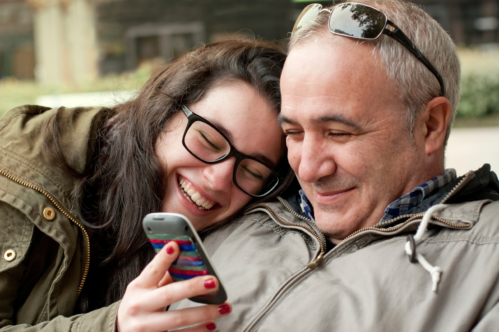 A father and his teenage daughter watching a video