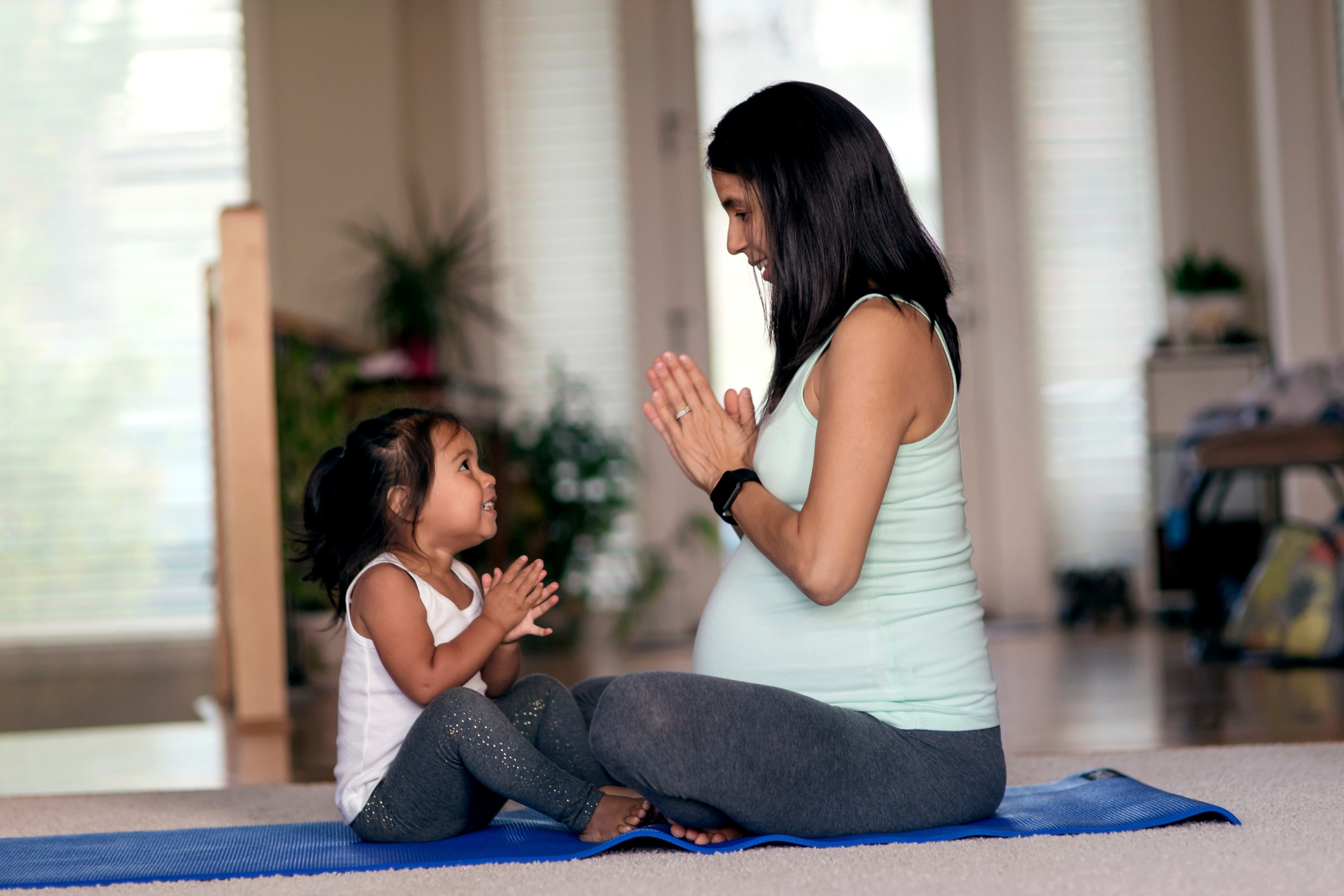 A mother and daughter meditating together on a yoga mat