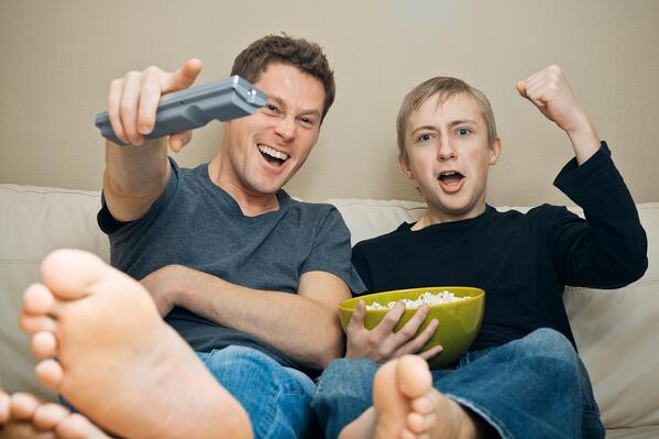 Father and teenager excited watching football