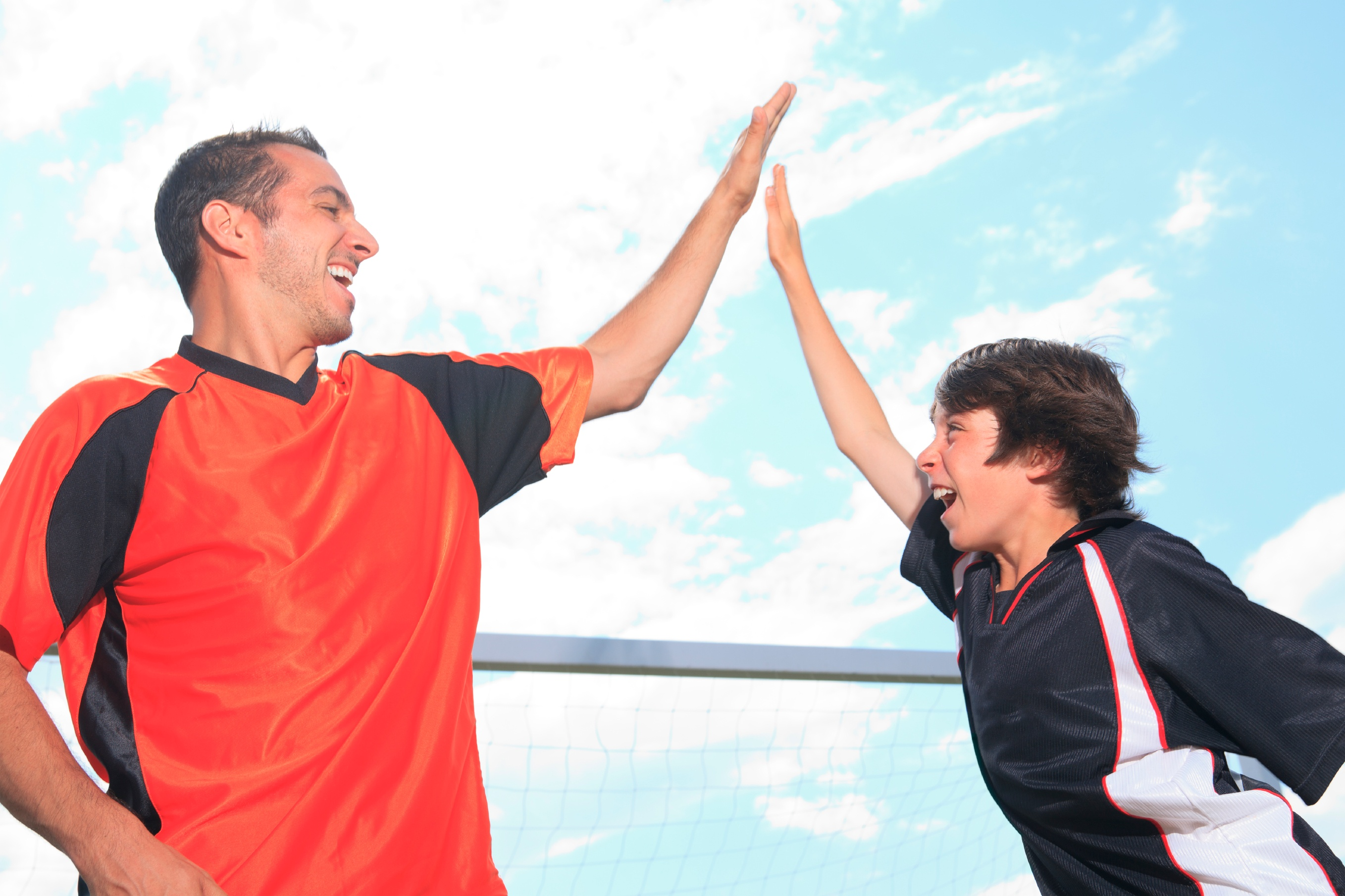 Father and son expressing elevated emotion as they high five each other