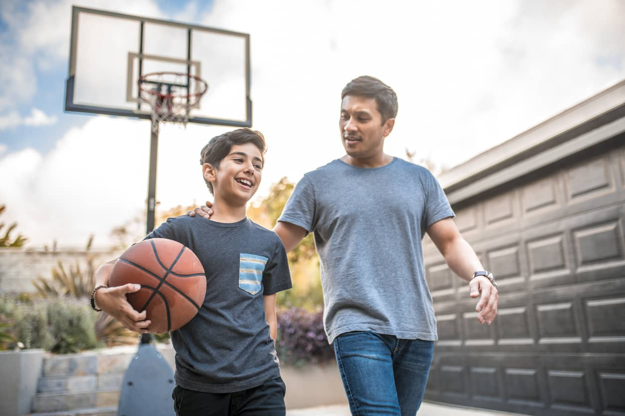 Teenage boy with his dad after playing basketball together