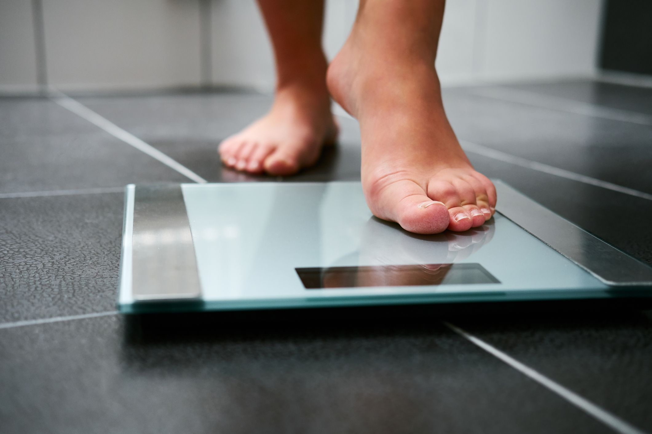 Bare-foot woman weighing herself