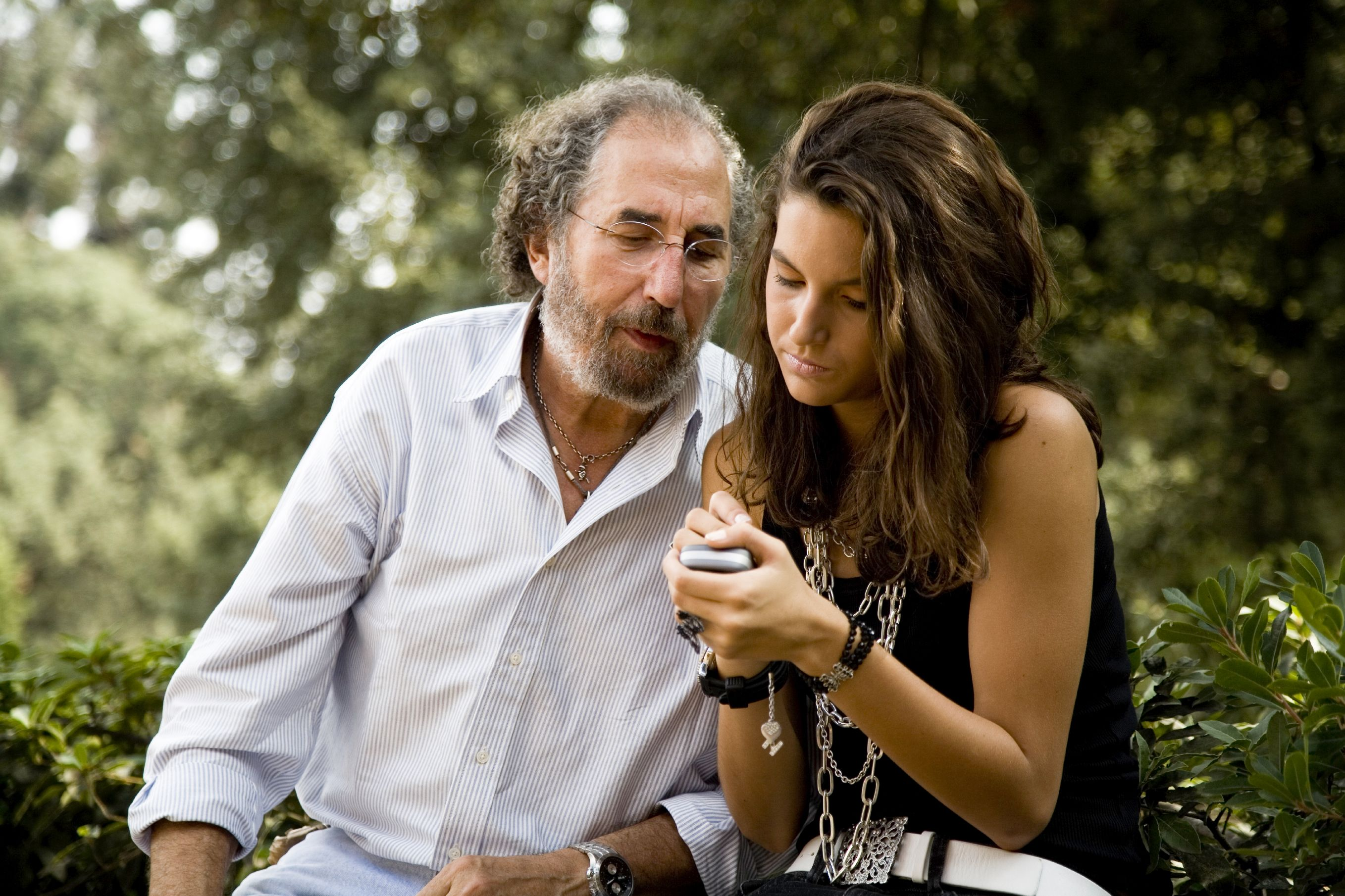 A teenager showing her grandfather an app on her phone
