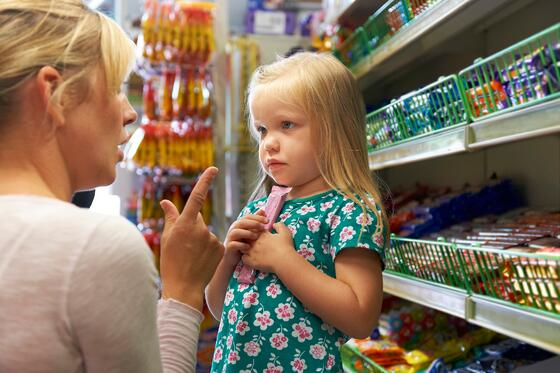 Mother scolding a little girl at the candy counter of a grocery store