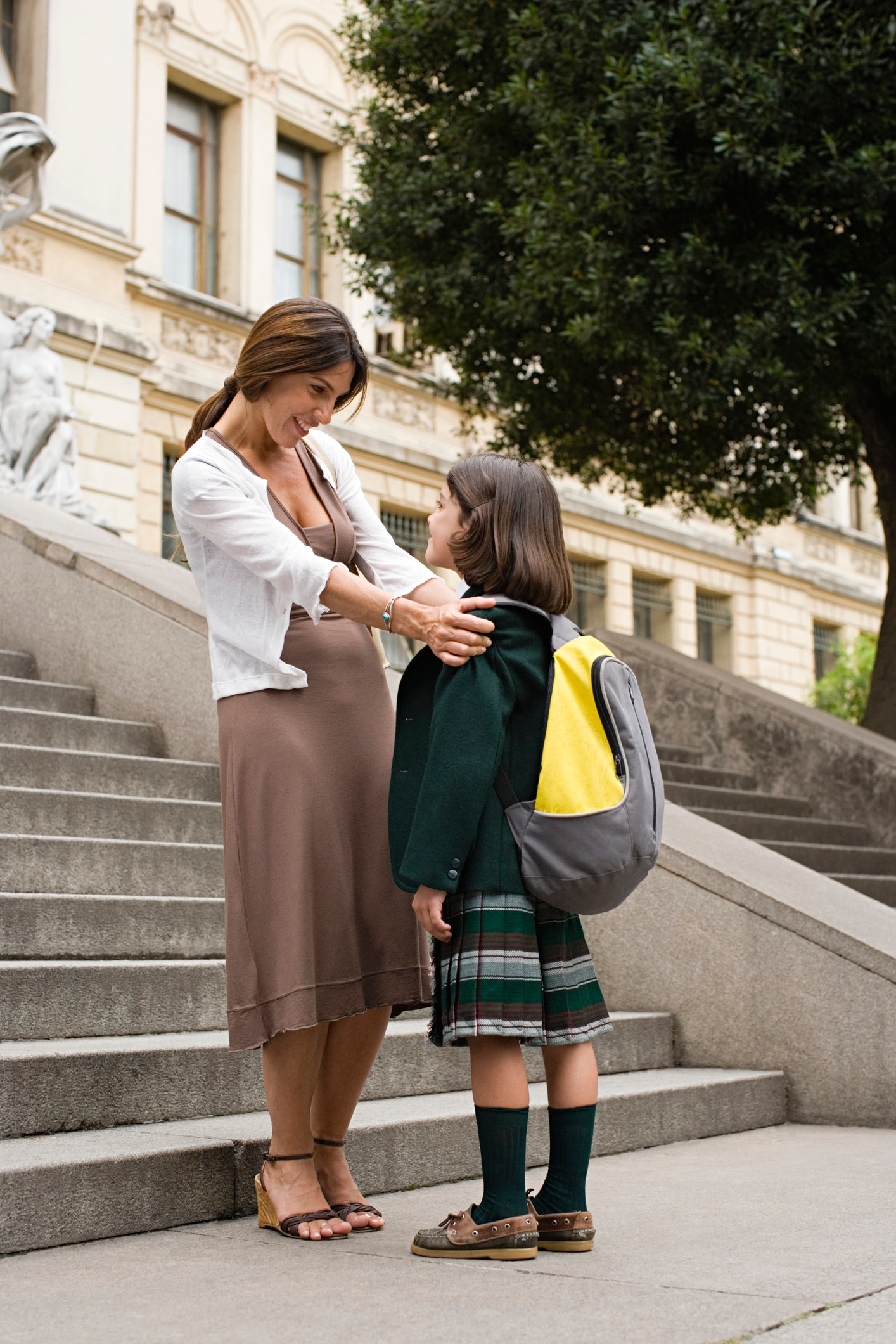 Mother greeting her daughter outside of school