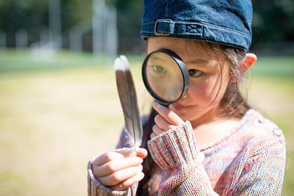 Young girl examining a feather with a magnifying glass