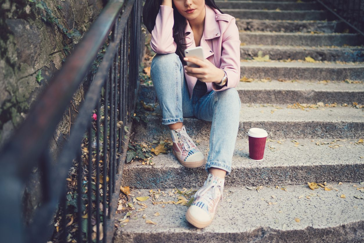 Teen sitting on steps with her smartphone