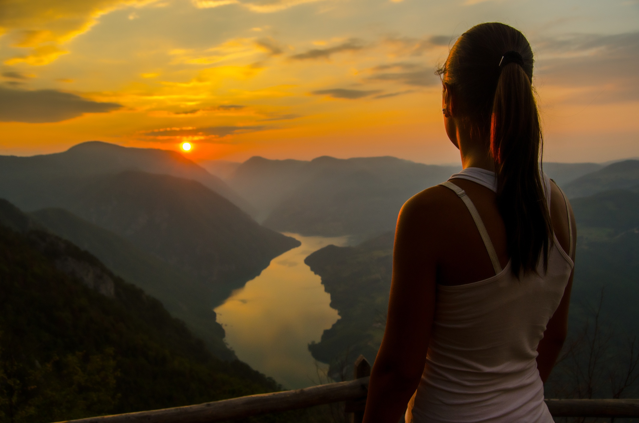 Girl watching the sunset at the top of the mountain