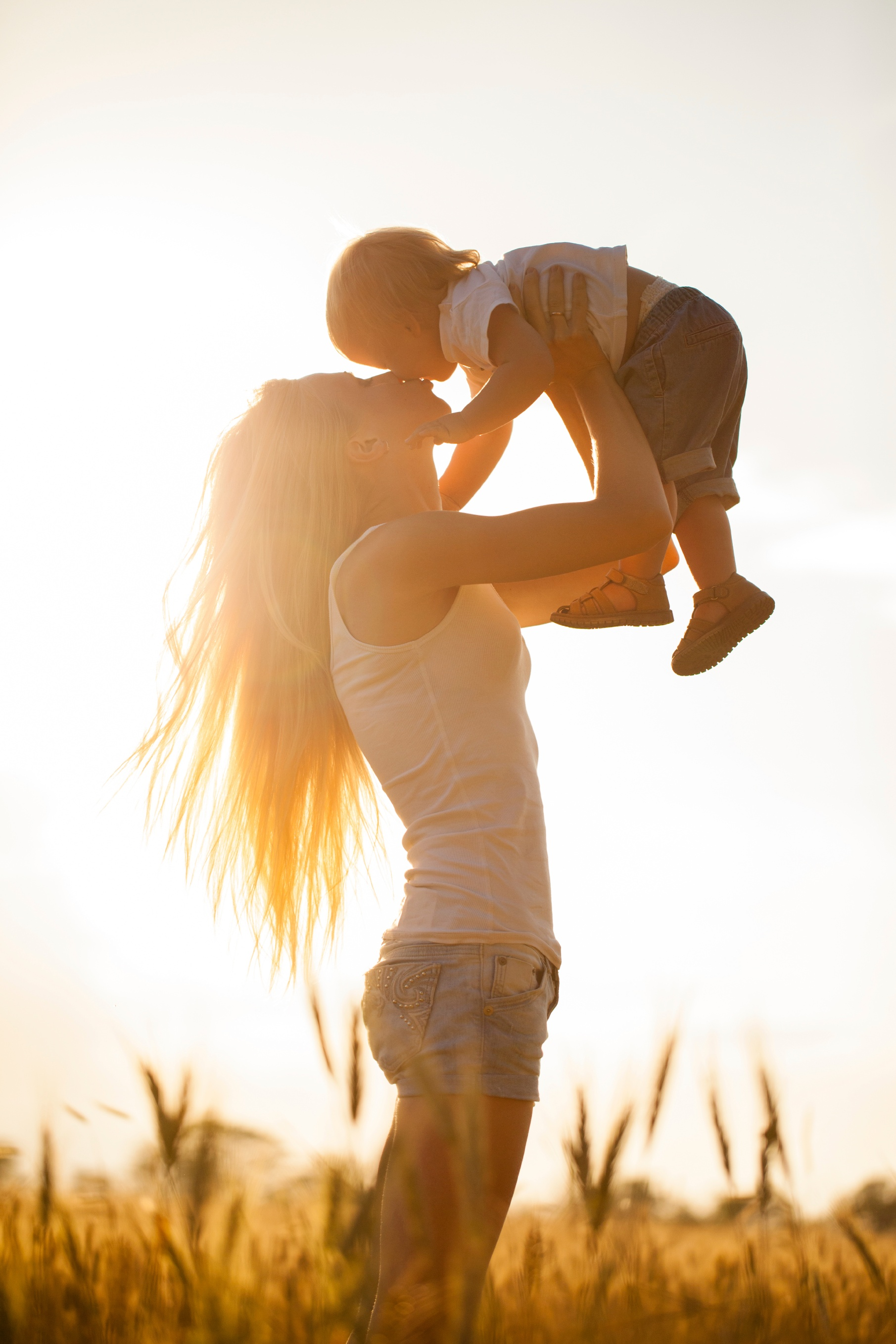 Happy mom lifting her child into the sunlit air