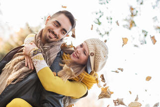 Happy couple piggybacking outdoors during autumn