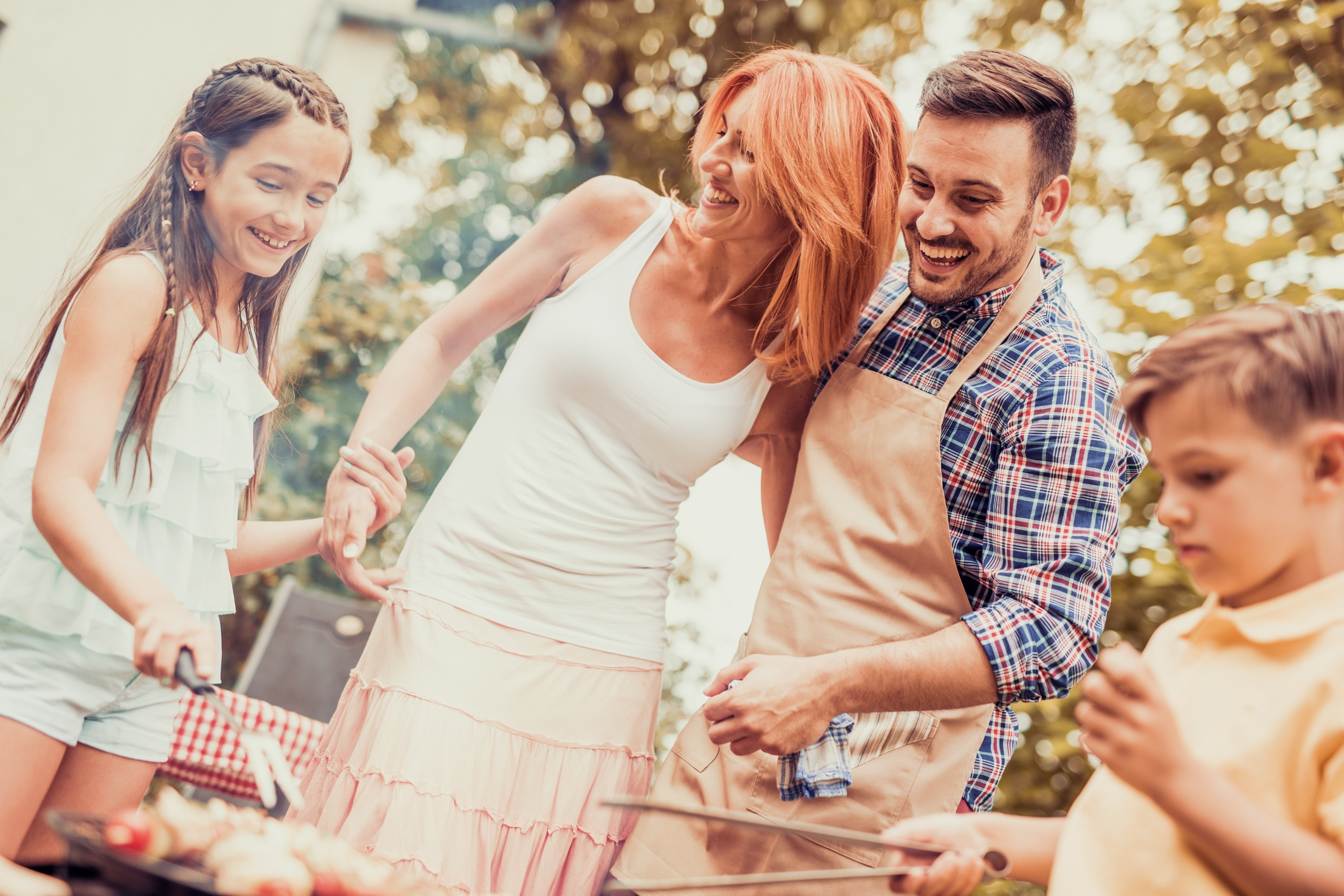Happy-young-family-barbecuing-meat-on-the-grill-831030944_2122x1416