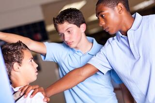 High school boys bullying a younger student against a locker
