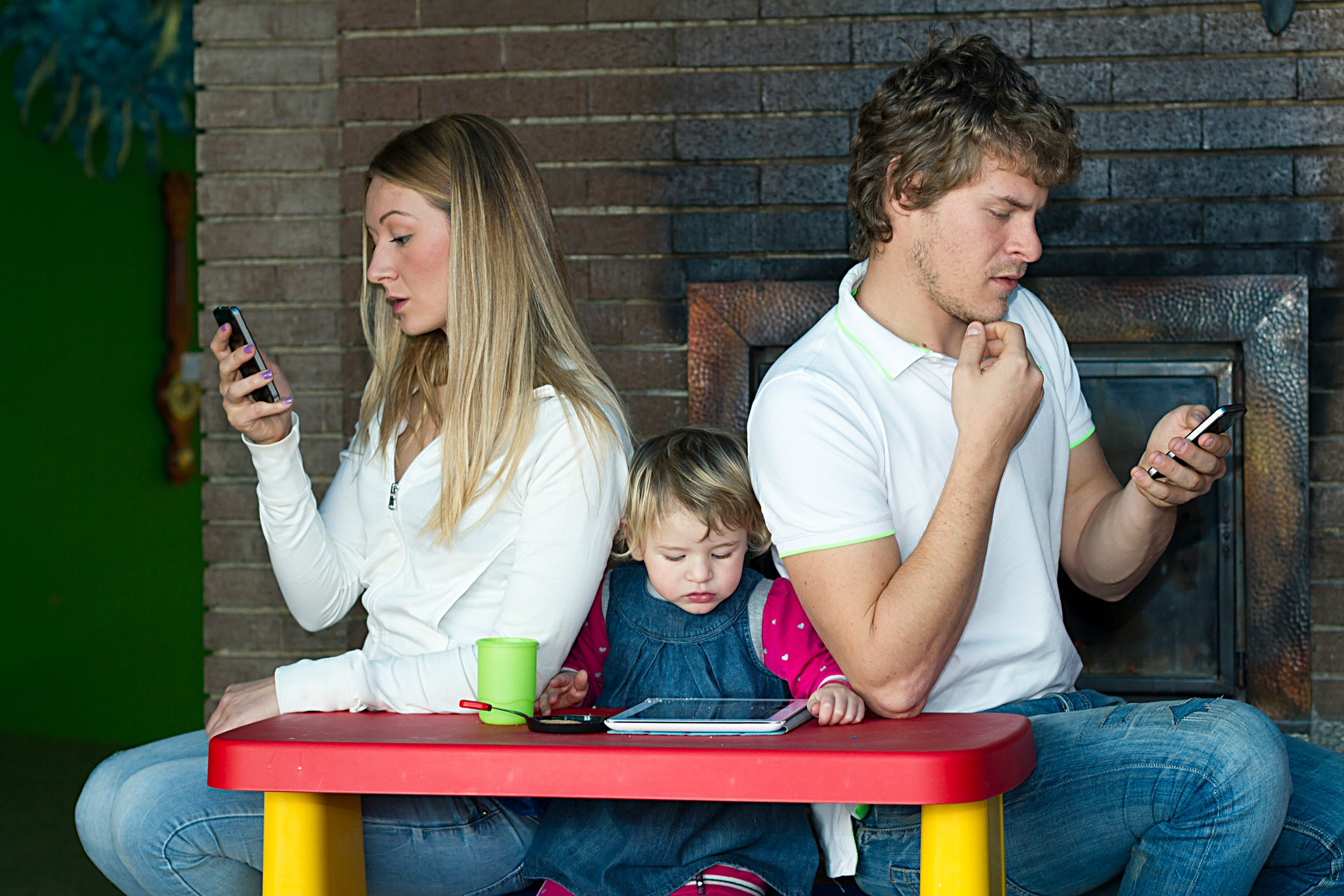 A couple locked into technology and ignoring their child