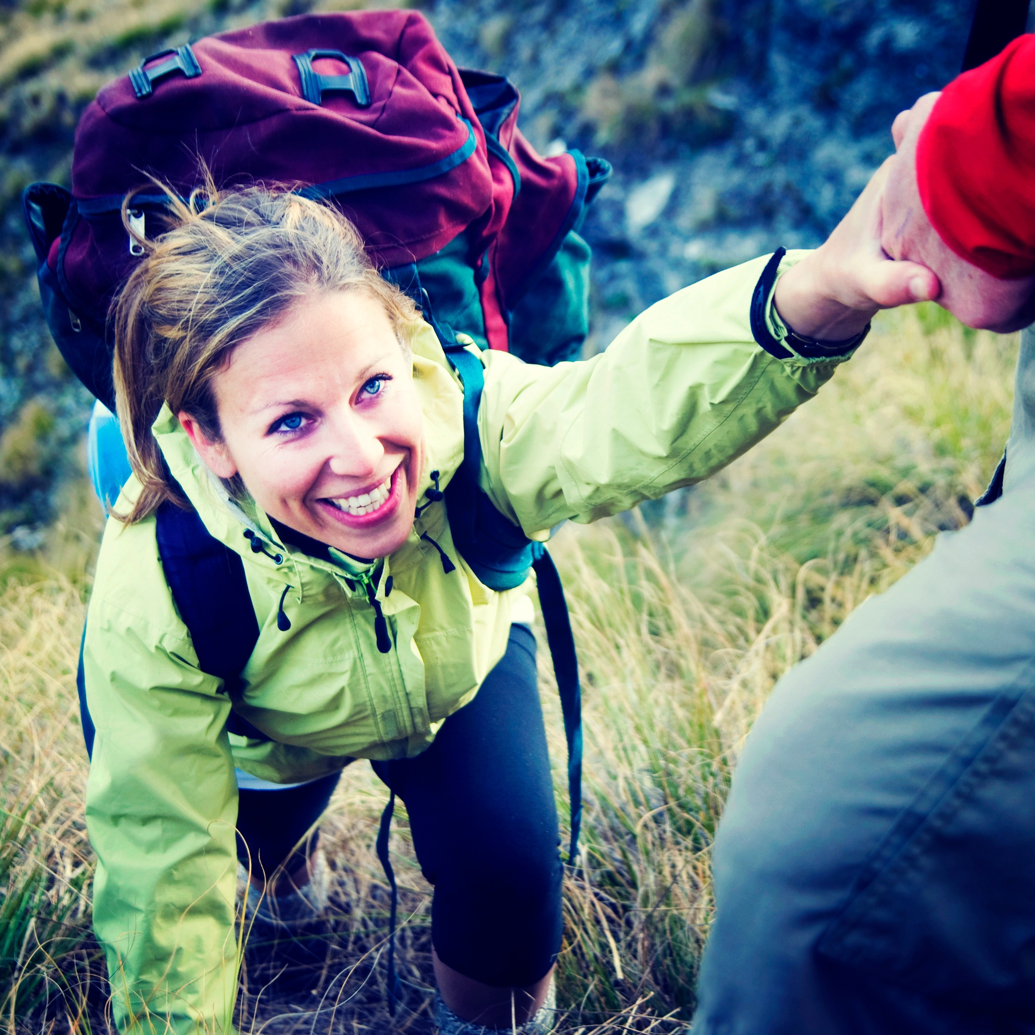 A woman accepting a lending hand of help on a hike