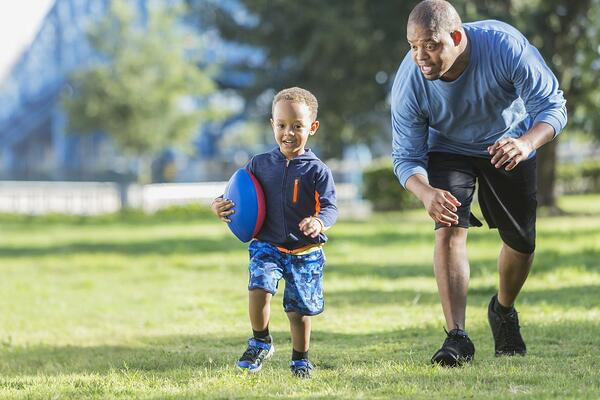A father chasing his son and exercising his gross motor