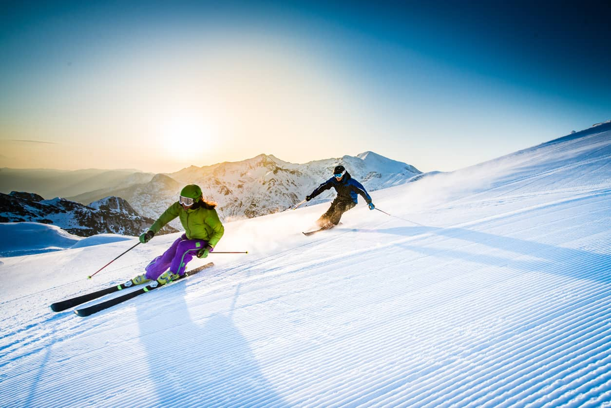 Young couple downhill skiing together