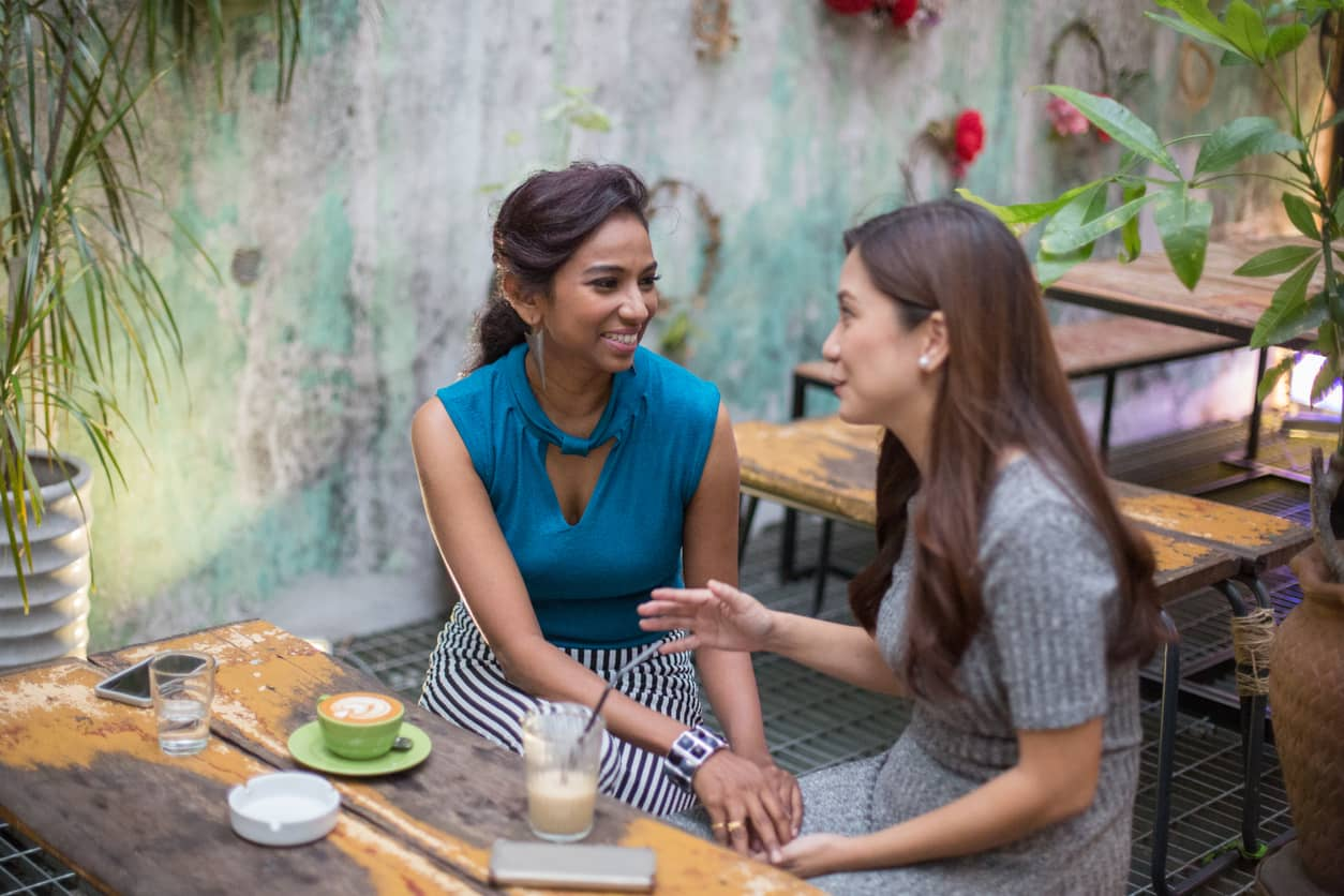 Two women gossiping at a cafe