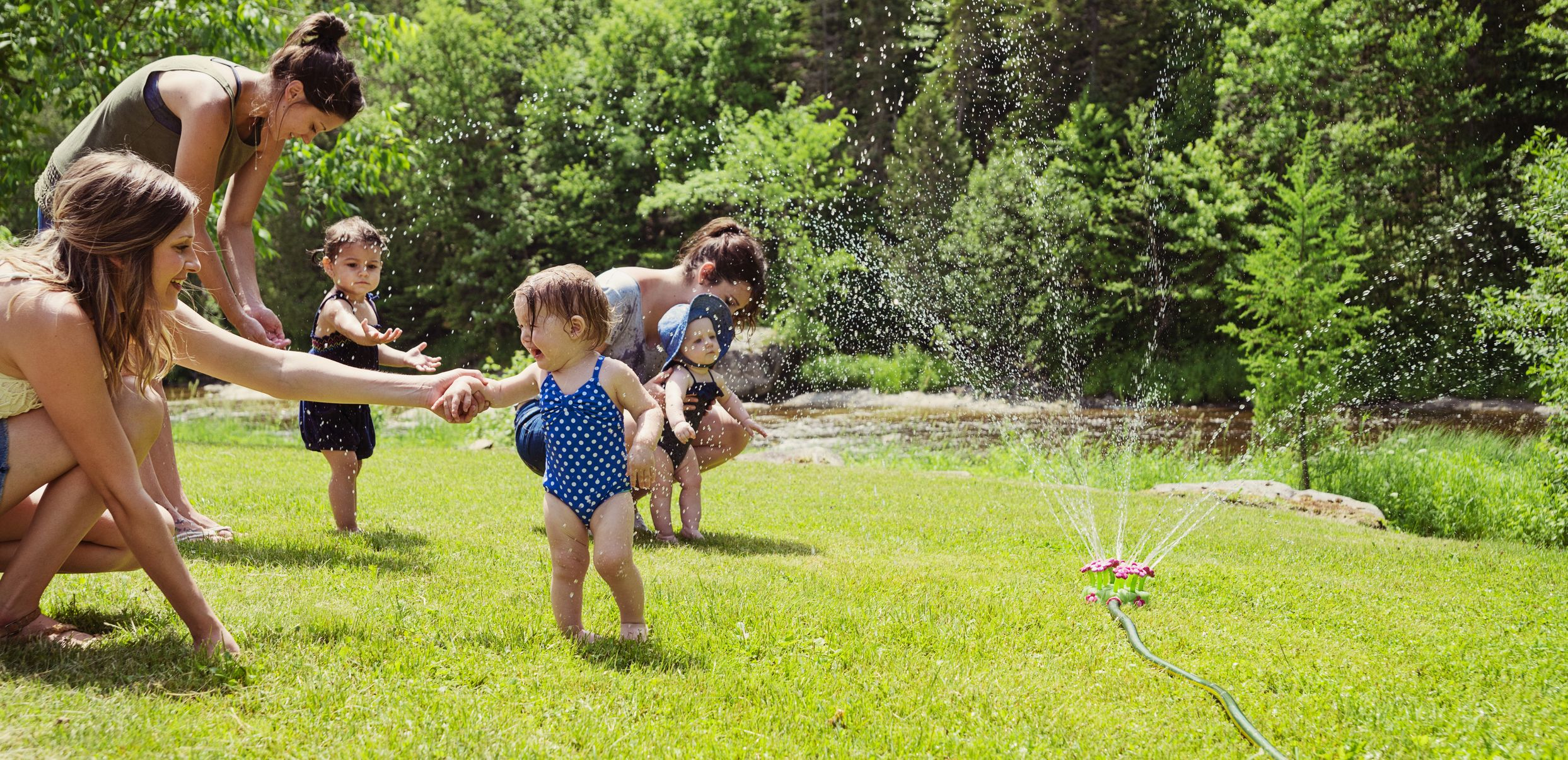 Mothers and children playing in the sprinkler.