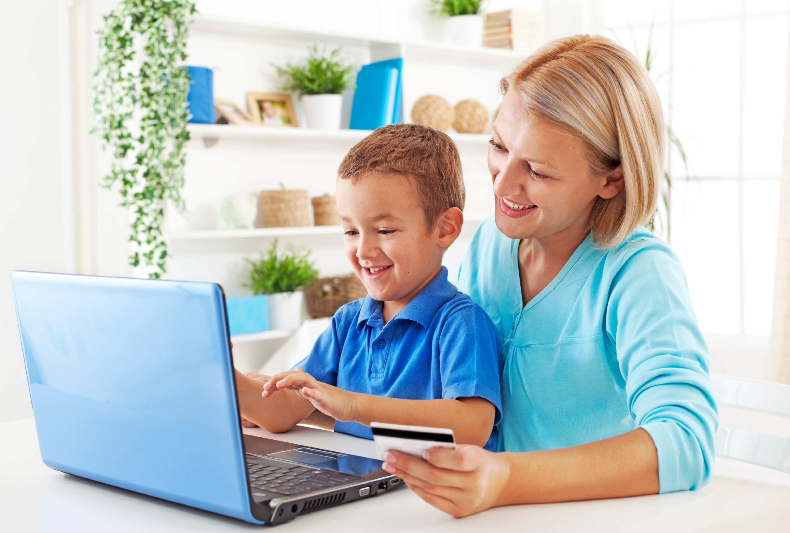 Mom helping boy on computer