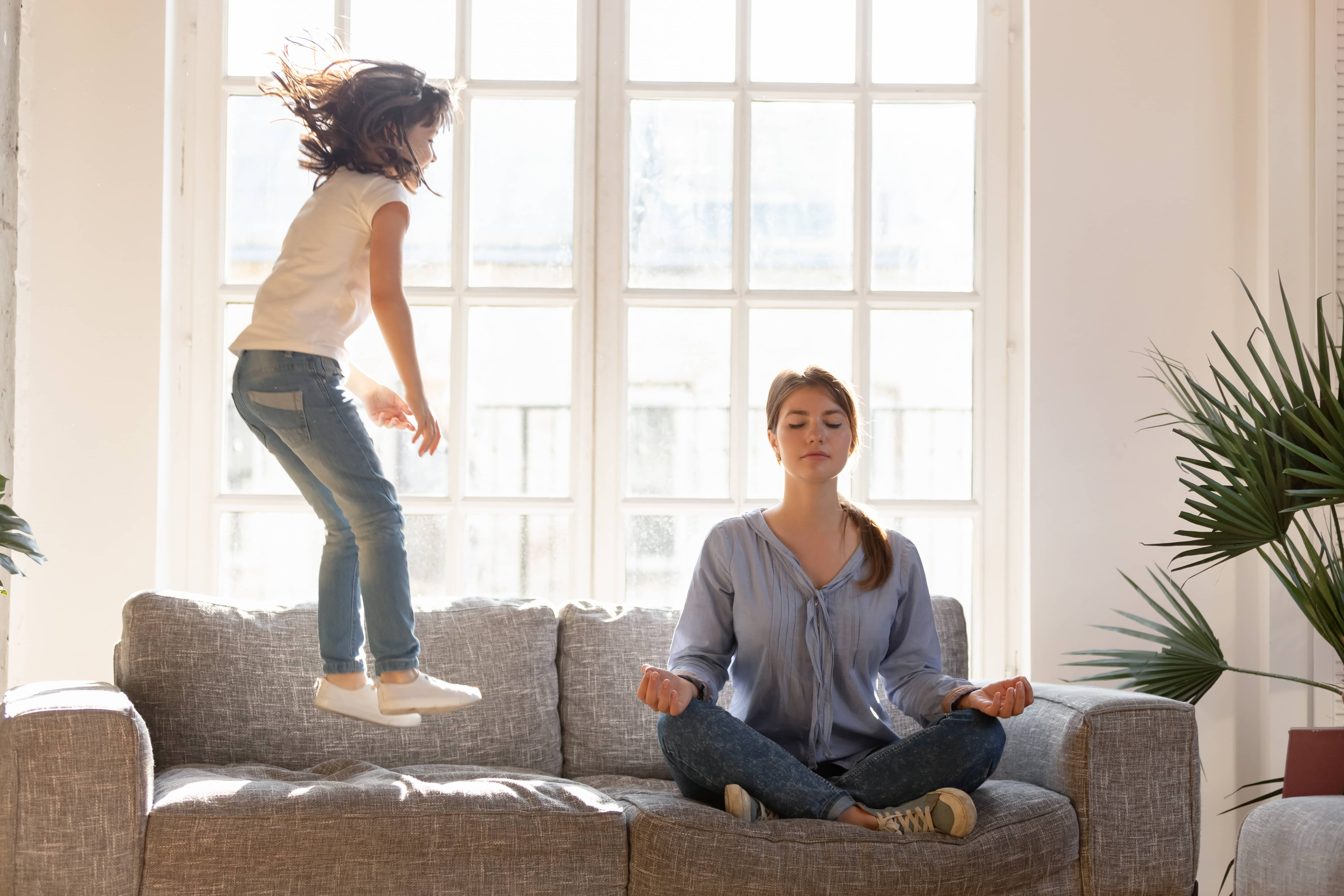 Mom in mindfulness practice as young girl jumps on couch