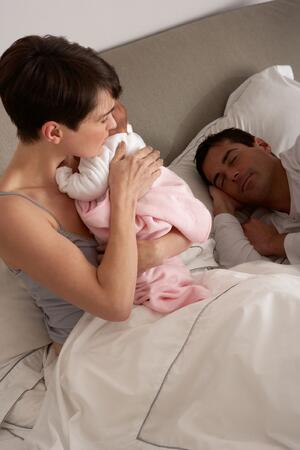 Mother-Cuddling-Newborn-Baby-In-Bed-At-Home-178865965_1415x2122-compressor