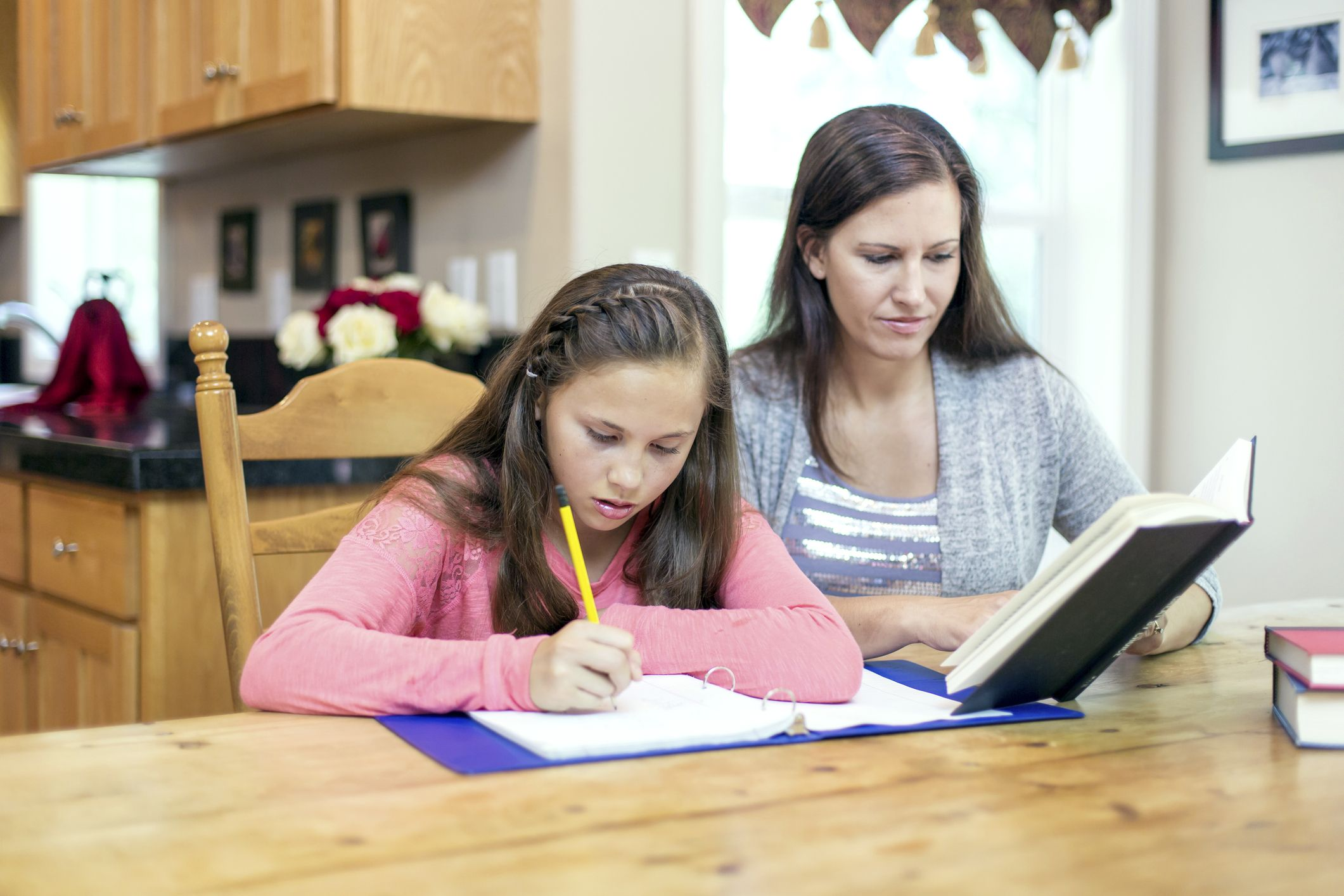 Mother helping her preteen with homework