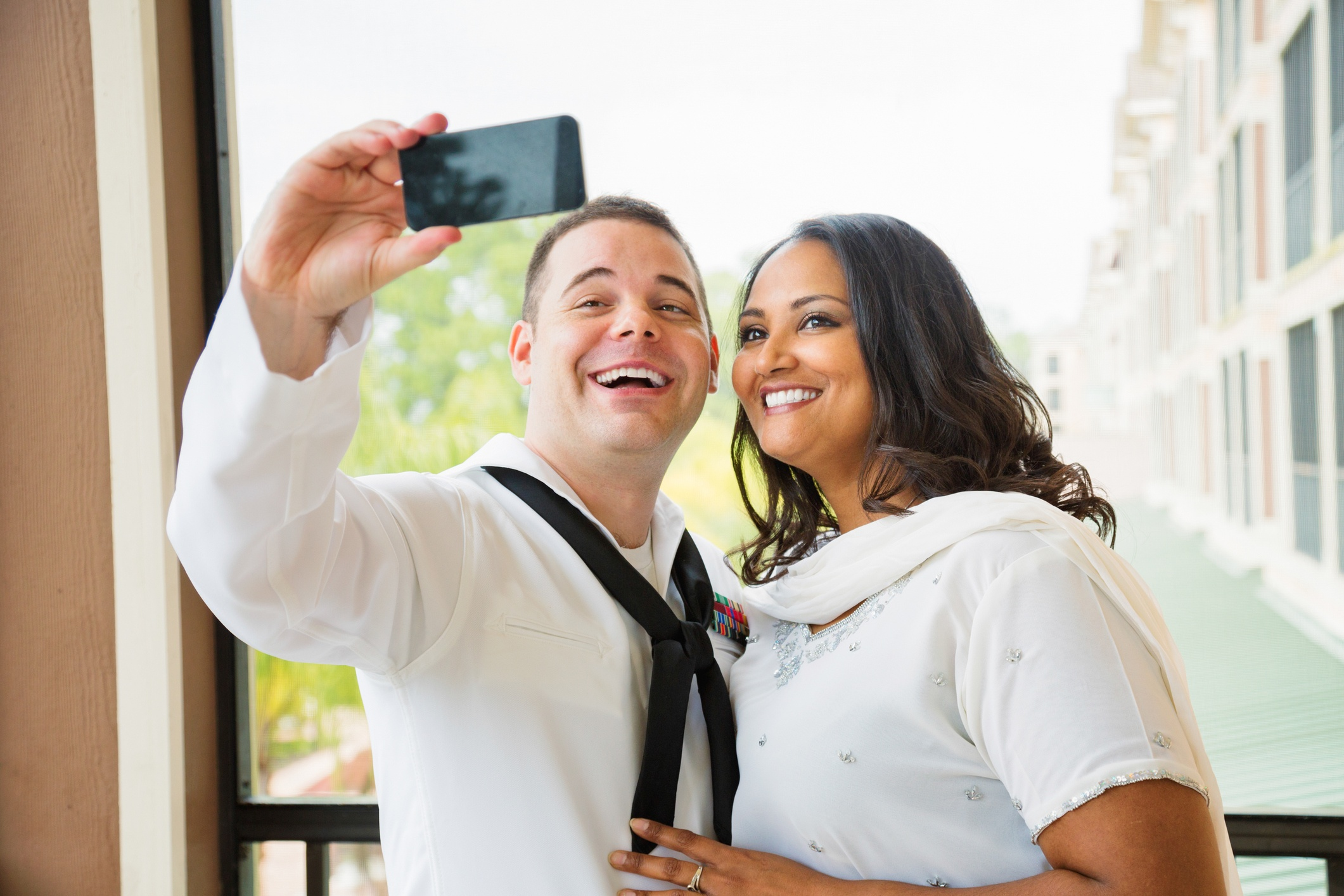 Newlywed American sailor shooting selfie with his wife