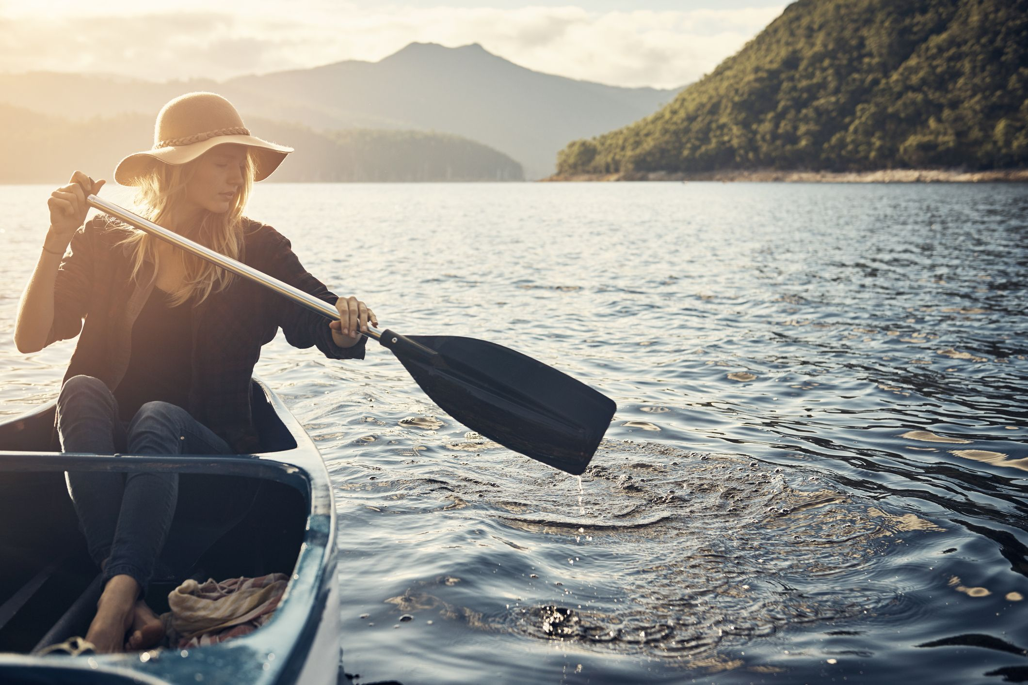 A woman boating on a lake for self-care and solitude