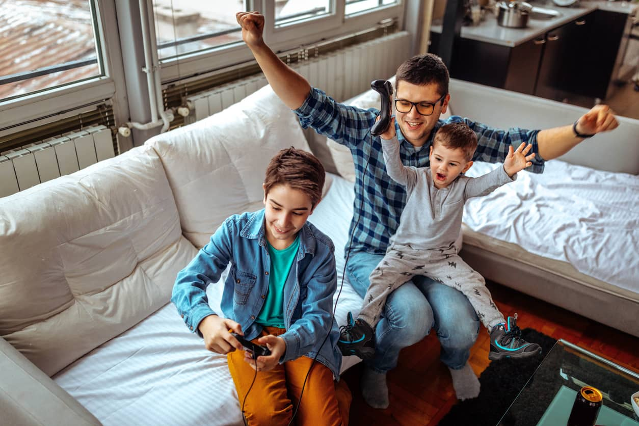 Father and sons gaming and celebrating