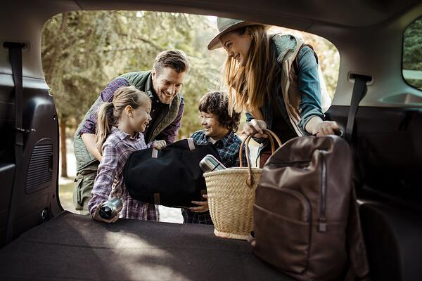 Blended family packing their car for a picnic