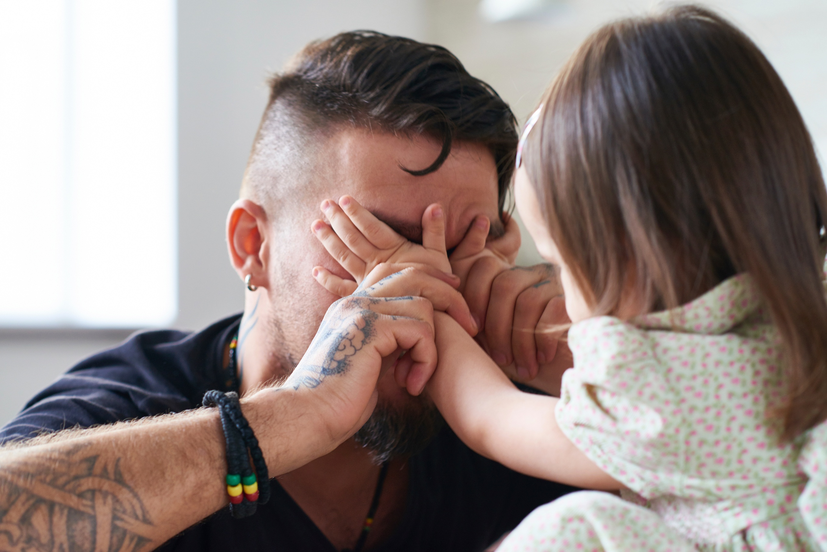 A father playing peek-a-boo with his toddler as a part of cognitive development