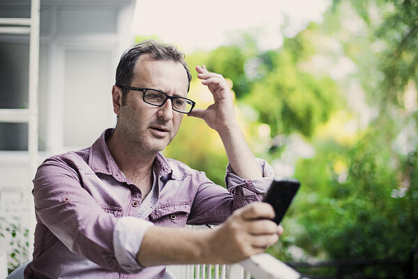 Concerned man reading the latest news on his smart phone