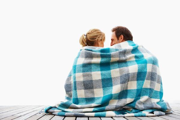 A young couple snuggled up in a blanket