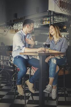 Loving couple laughing over a glass of wine