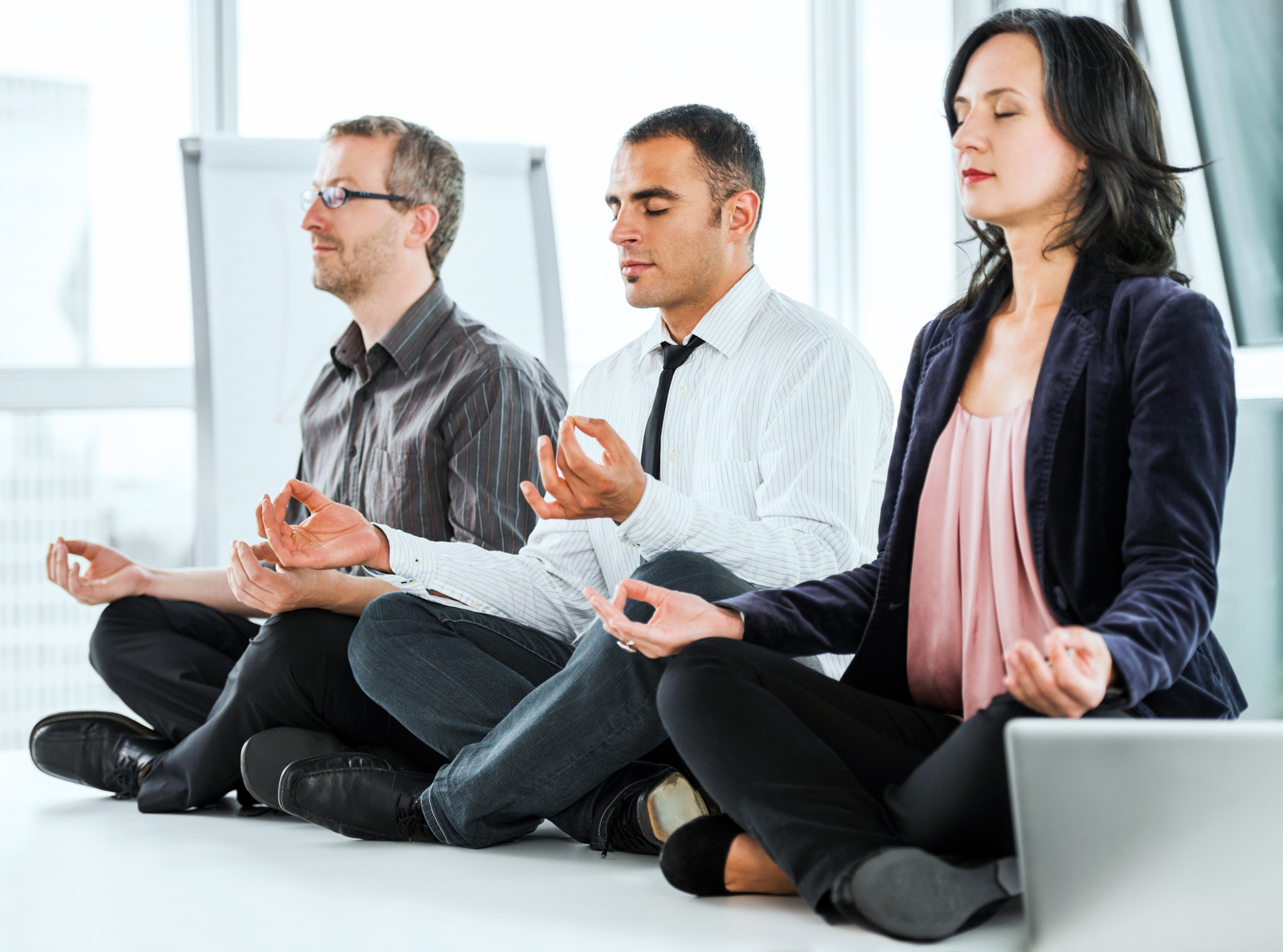 Successful businesspeople meditating in the office