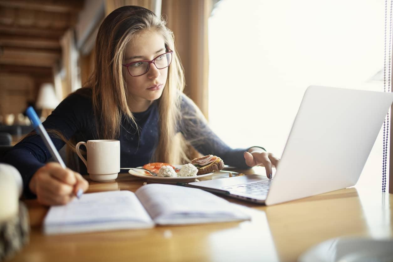 Teenage girl doing her homework at breakfast