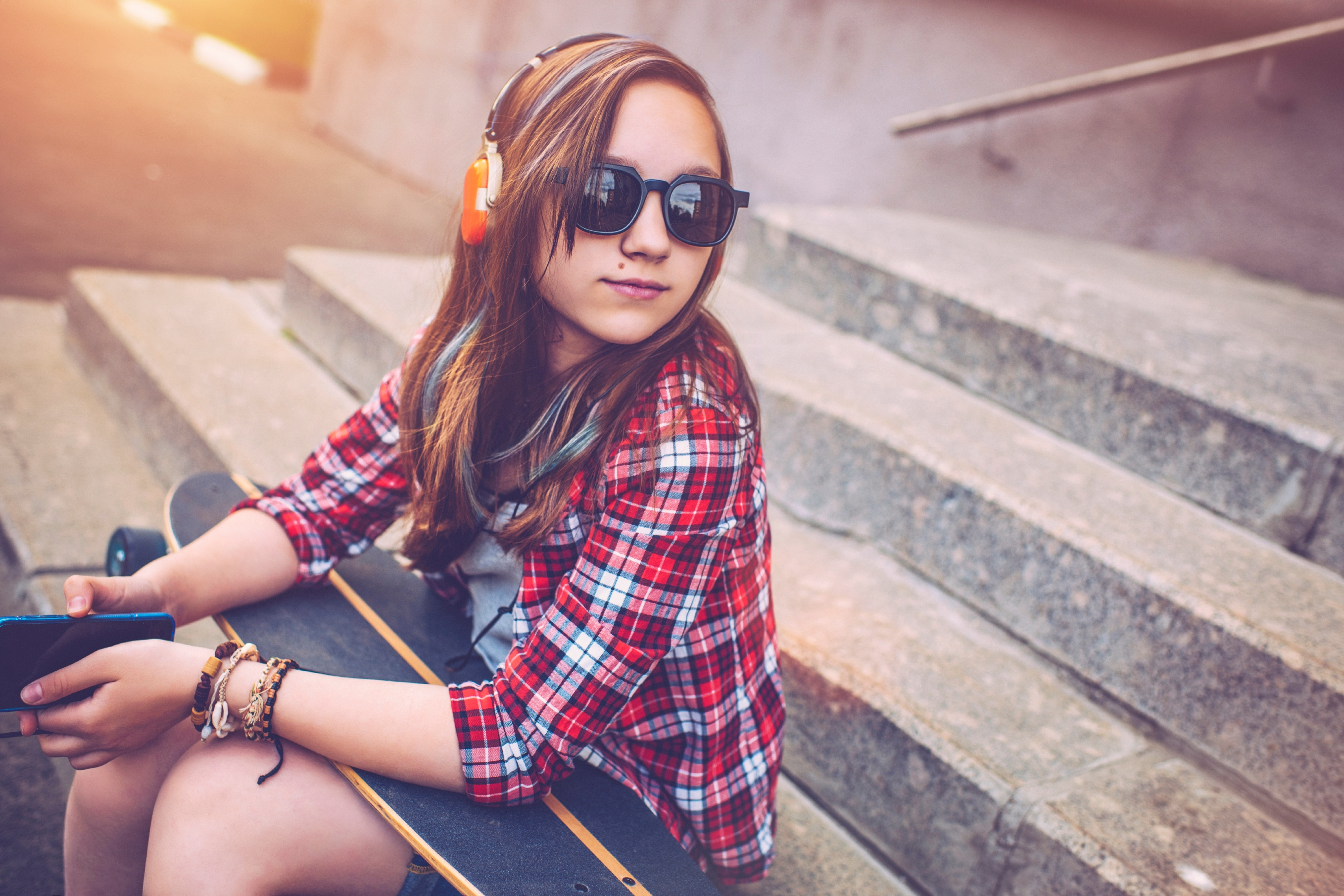 Teenage girl with a skateboard listening to music