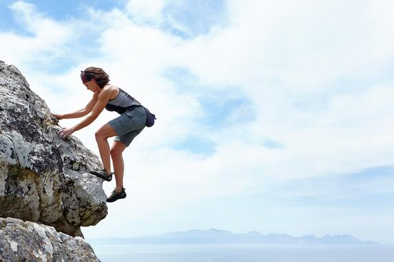 Don't climb the mountain of life alone; a woman mountain climbing alone