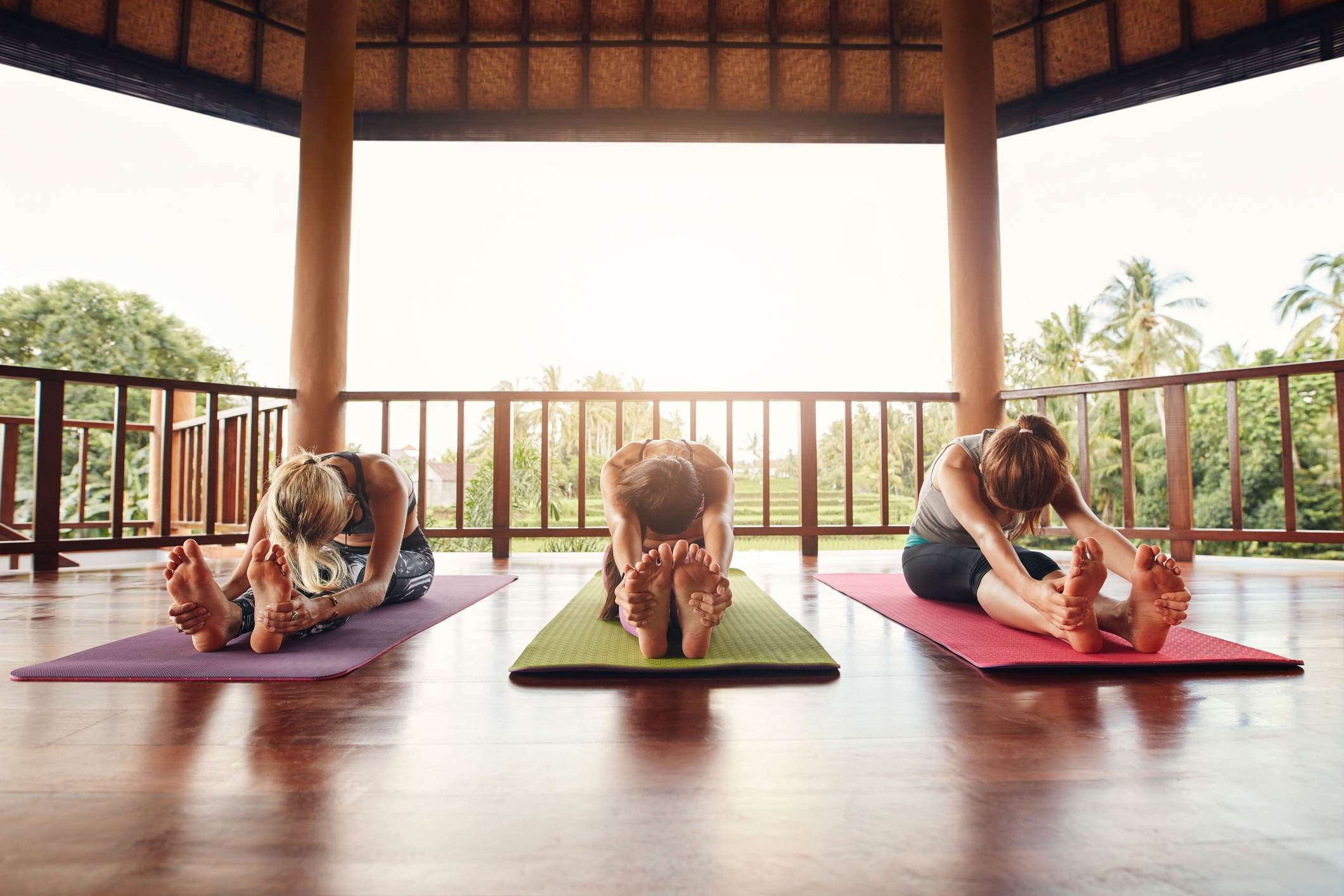 Three women stretching at a yoga class