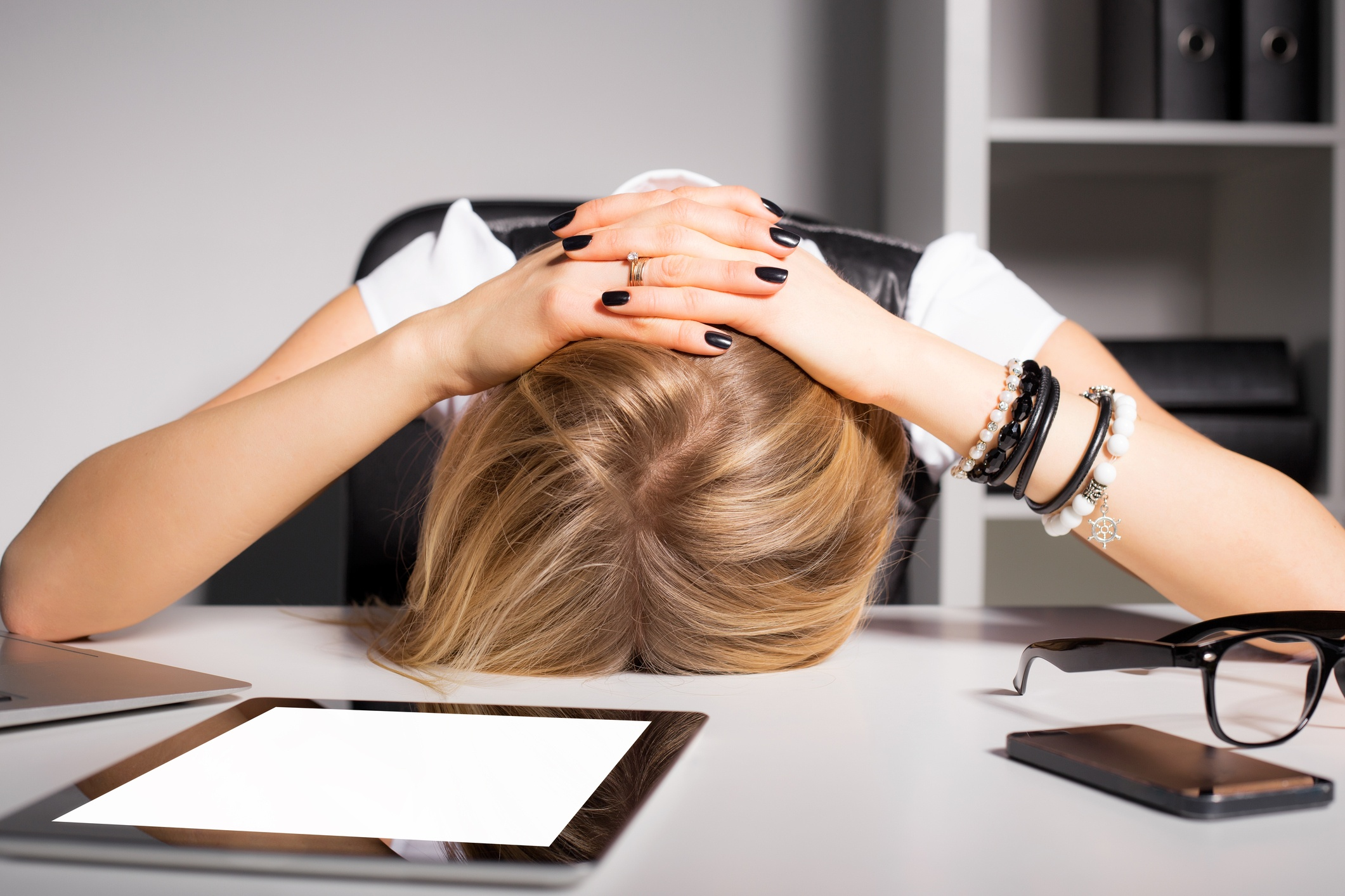 Tired and overwhelmed business woman resting her head on her desk